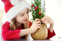 Adorable little girl wearing Santa hat decorating small Christmas tree in a pot on Christmas morning Royalty Free Stock Photos