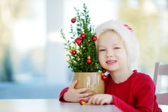 Adorable little girl wearing Santa hat decorating small Christmas tree in a pot on Christmas morning Royalty Free Stock Photo