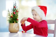 Adorable little girl wearing Santa hat decorating small Christmas tree in a pot on Christmas morning Royalty Free Stock Images
