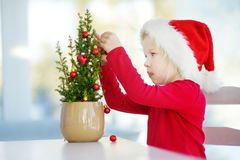 Adorable little girl wearing Santa hat decorating small Christmas tree in a pot on Christmas morning Stock Photo