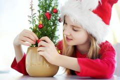 Adorable little girl wearing Santa hat decorating small Christmas tree in a pot on Christmas morning Stock Images