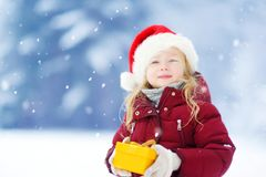 Adorable little girl wearing Santa hat holding Christmas gift on beautiful winter day Royalty Free Stock Photo