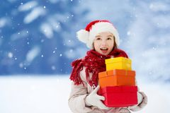 Adorable little girl wearing Santa hat holding a pile of Christmas gifts on beautiful winter day Stock Photo