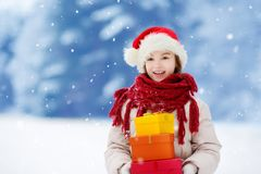 Adorable little girl wearing Santa hat holding a pile of Christmas gifts on beautiful winter day Stock Images