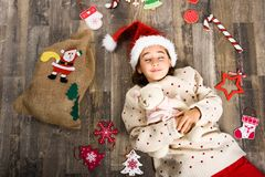 Adorable little girl wearing santa hat laying on wooden floor. Adorable little girl wearing santa hat sleeping on wooden floor with Christmas ornaments. Winter Stock Photos
