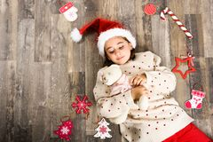 Adorable little girl wearing santa hat laying on wooden floor. Adorable little girl wearing santa hat smiling on wooden floor with Christmas ornaments. Winter Stock Image