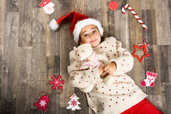 Adorable little girl wearing santa hat laying on wooden floor. Adorable little girl wearing santa hat smiling on wooden floor with Christmas ornaments. Winter Stock Photography