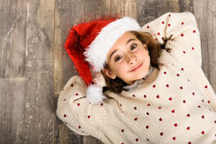 Adorable little girl wearing santa hat laying on wooden floor. Adorable little girl wearing santa hat smiling on wooden floor. Winter clothes for Christmas Royalty Free Stock Image