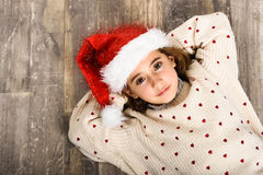 Adorable little girl wearing santa hat laying on wooden floor. Winter clothes for Christmas Stock Photo