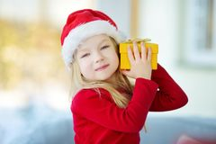 Adorable little girl wearing Santa hat opening a giftbox on Christmas morning Royalty Free Stock Photo