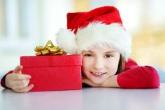 Adorable little girl wearing Santa hat opening a giftbox on Christmas morning Royalty Free Stock Image