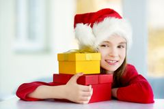Adorable little girl wearing Santa hat opening a giftbox on Christmas morning Royalty Free Stock Photos