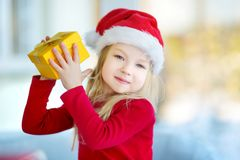 Adorable little girl wearing Santa hat opening a giftbox on Christmas morning Royalty Free Stock Photography