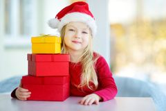 Adorable little girl wearing Santa hat opening a giftbox on Christmas morning Stock Photo