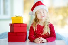 Adorable little girl wearing Santa hat opening a giftbox on Christmas morning Royalty Free Stock Images