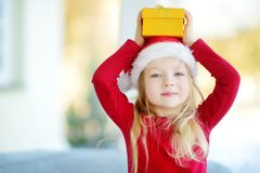 Adorable little girl wearing Santa hat opening a giftbox on Christmas morning Stock Photography
