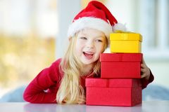 Adorable little girl wearing Santa hat opening a giftbox on Christmas morning Stock Images