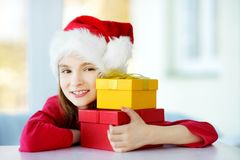 Adorable little girl wearing Santa hat opening a giftbox on Christmas morning Stock Photos