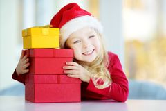 Adorable little girl wearing Santa hat opening a giftbox on Christmas morning Stock Image