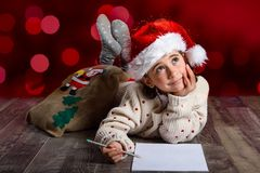 Adorable little girl wearing santa hat writing Santa letter. On wooden floor. Winter clothes for Christmas. Red bokeh at the background Royalty Free Stock Images