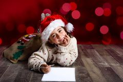 Adorable little girl wearing santa hat writing Santa letter. On wooden floor. Winter clothes for Christmas. Red bokeh at the background Royalty Free Stock Photography