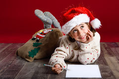 Adorable little girl wearing santa hat writing Santa letter. On wooden floor. Winter clothes for Christmas Stock Image