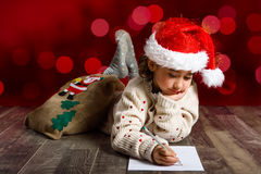 Adorable little girl wearing santa hat writing Santa letter. On wooden floor. Winter clothes for Christmas. Red bokeh at the background Stock Image