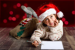 Adorable little girl wearing santa hat writing Santa letter. On wooden floor. Winter clothes for Christmas. Red bokeh at the background Royalty Free Stock Photo