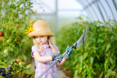 Adorable little girl wearing straw hat and childrens garden gloves playing with her toy garden tools in a greenhouse. On sunny summer day royalty free stock photos