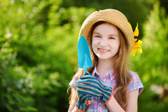 Adorable little girl wearing straw hat holding garden tools Stock Image