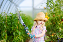 Adorable little girl wearing straw hat holding garden tools Stock Photos