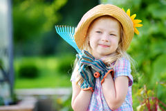 Adorable little girl wearing straw hat holding garden tools Royalty Free Stock Images