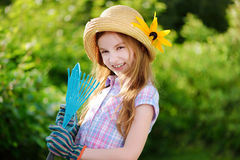 Adorable little girl wearing straw hat holding garden tools Stock Images