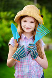 Adorable little girl wearing straw hat holding garden tools Royalty Free Stock Photography