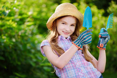 Adorable little girl wearing straw hat holding garden tools Royalty Free Stock Photos