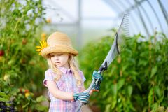 Adorable little girl wearing straw hat holding garden tools Stock Photo