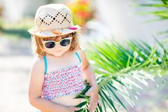 Close-up portrait of adorable little girl at the tropical resort, hiding behind the palm at the sunny summer day. Adorable little girl wearing sunglasses and stock photos