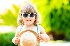 Close-up portrait of adorable little girl at the tropical resort, palm trees at the background, sunny summer day. Adorable little girl wearing sunglasses and stock photo