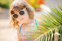 Close-up portrait of adorable little girl at the tropical resort, hiding behind the palm at the sunny summer day. Adorable little girl wearing sunglasses stock photos