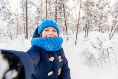 Little girl outdoors on winter. Adorable little girl wearing warm clothes outdoors on beautiful winter snowy day taking selfie Stock Photo