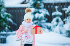 Adorable little girl wearing warm clothes outdoors on Christmas day holding gift and skates. Adorable little girl wearing warm clothes outdoors on Christmas day Royalty Free Stock Photo
