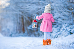Adorable little girl wearing warm coat outdoors on Christmas day holding flashlight Royalty Free Stock Photography