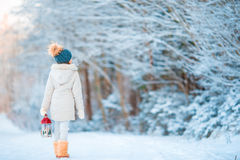 Adorable little girl wearing warm coat outdoors on Christmas day holding flashlight walking Stock Image