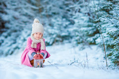 Adorable little girl wearing warm coat outdoors on Christmas day warms cold hands by flashlight stock photo