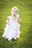Adorable Little Girl Wearing White Dress In A Grass Field Royalty Free Stock Photography