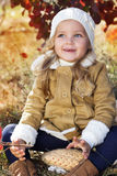 Adorable little girl is wearing winter clothes. With autumn leaves on the nature Stock Image