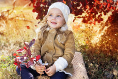 Adorable little girl is wearing winter clothes. Adorable happy little girl is wearing winter clothes with autumn leaves on the nature Stock Image