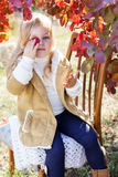 Adorable little girl is wearing winter clothes. Adorable happy little blonde girl is wearing winter clothes is sitting on the chair with autumn leaves on the Royalty Free Stock Photos