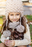 Adorable little girl is wearing winter clothes. Adorable happy little girl is wearing knitted hat with autumn leaves on the nature Stock Images