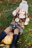 Adorable little girl is wearing winter clothes. Adorable happy little girl is wearing knitted hat sitting on pumpkin with autumn leaves on the nature Royalty Free Stock Photo